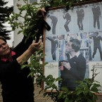 A relative of the deceased golfer fixes a black ribbon beside a poster outside the chapel.