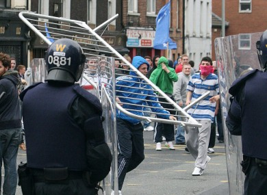 Protestors throw a barrier at Garda in a street in Dublin during skirmishes this afternoon, in which 21 people were arrested.