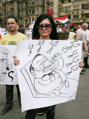 A woman holds a poster illustrating former Egyptian President Hosni Mubarak during a pro-democracy demonstration at Tahrir Square on Friday.