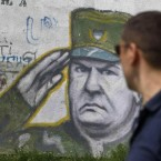 A boy walks pass graffiti of war crimes fugitive Bosnian Serb army commander Ratko Mladic in Belgrade, Serbia. He was arrested this week after 16 years on the run. (AP Photo/Andrej Cukic)