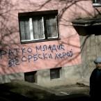 A woman passes by graffiti that reads
