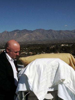 Mark Kelly, stands with his wife Gabrielle Giffords as she looks from her bed at the Santa Catalina Mountains while on an outdoor deck at University Medical Center in Tucson, Arizona in January.