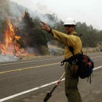 A firefighter directs his crew during a backburn operation to fight the Wallow Fire in Nutrioso, Arizona. (AP Photo/Marcio Jose Sanchez)
