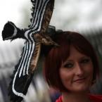 A female racegoer with a bird-themed hat<span class=