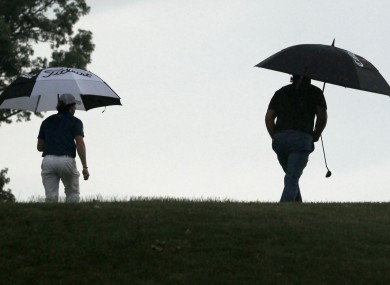 Rory McIlroy, of Northern Ireland, left, and Phil Mickelson, walk over the hill to the ninth green during the first round of the US Open.