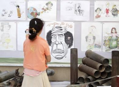 A Libyan girl in Misrata looks at anti-Gaddafi caricatures on 21 June 2011.