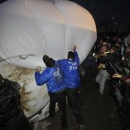 Security staff and members of direct action group Art Uncut, tussle over a 20ft balloon emblazoned with the message