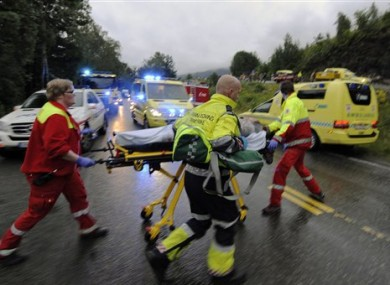 Emergency response personnel escort an injured person from the camp site on Utoya.