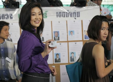 Thai opposition party leader Yingluck Shinawatra showing her ID card before polling today.