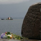 Flowers are seen on the shore opposite to the Island Utoya, Norway, today as the search continues in for victims of Friday's shooting. (AP Photo/Frank Augstein)