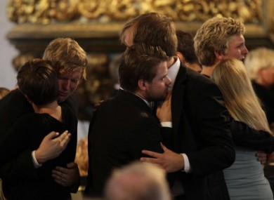 People embrace at the end of today's memorial service at Oslo Cathedral.