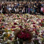 People lay floral tributes at the end of a memorial service outside at Oslo Cathedral. (AP Photo/Emilio Morenatti)