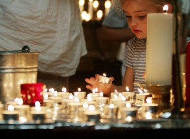 A child lights a candle after a special London prayer service for the two terrorist attacks in Norway.