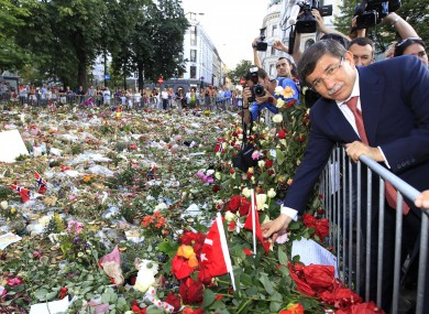Turkey's foreign minister Ahmet Davutoglu lays flowers and Turkish flags as a tribute in memory of the victims of July 22, at a cathedral earlier this month. Norway today marked the end of a month of mourning for the 77 victims.