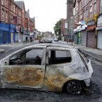 A woman cycles past a burnt out car on Lawrence road in Wavertree, Liverpool, after a second night of rioting.