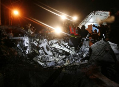 Palestinians look at the wreckage of a car after it was hit by an Israeli missile, killing an Islamic Jihad militant in Gaza.