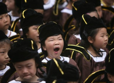 Pupils in traditional costume photographed during a school enrolment ceremony in Nanjing, China, today.