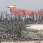 An air tanker drops fire retardant on a hot spot in an area destroyed by a wildfire at Possum Kingdom Lake, Texas. (AP Photo/LM Otero)