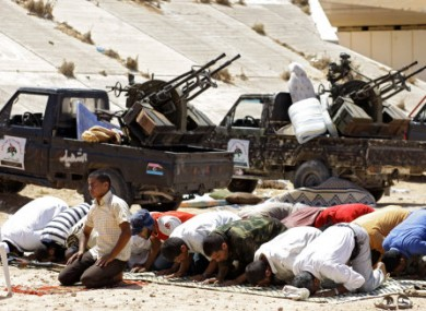 Rebel fighters pray at a last rebel checkpoint some 80 kilometers east from rebel-held Misrata