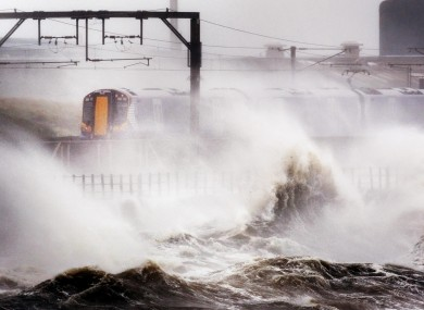 A train continues its journey in North Ayrshire, Scotland amid heavy winds and strong waves brought by Hurricane Katia.