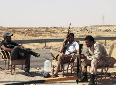 Revolutionary fighters sit at a checkpoint outside Sirte, Libya, today.
