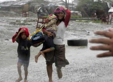 A family flees their home in Manila today during Typhoon Nesat.