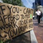 Businessmen walk past the Occupy Boston encampment in Boston's financial district on Friday. (AP Photo/Michael Dwyer/PA)