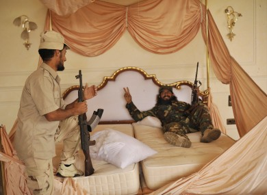 Rebels rest in the bed of Gaddafi's palace in Sirte after making further gains.