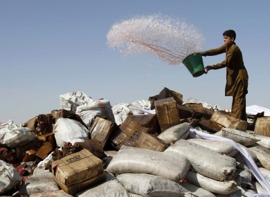 A man pours petrol over a pile of confiscated drugs and alcohol in Afghanistan