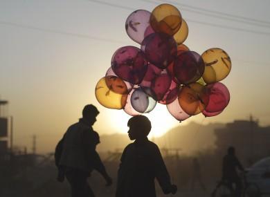Balloon seller Mahfouz Bahbah, 12, at a roadside in Afghanistan