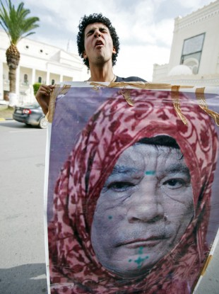 A Libyan man reacts as he holds a photo of Muammar Gaddafi, manipulated to show the leader dressed as a woman, in Tripoli today.