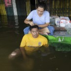 A Thai woman sitting on a table to keep her dry pulls gray hairs for her friend sitting in floodwater in Bangkok yesterday. (AP Photo/Sakchai Lalit)