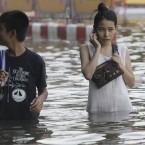 Thai residents wade through floodwaters beside homemade measure stick in Bangkok yesterday. (AP Photo/Sakchai Lalit)