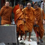 Buddhist monks make their way on a side walk of a flooded road near Mahathat temple in Bangkok yesterday. (AP Photo/Apichart Weerawong)
