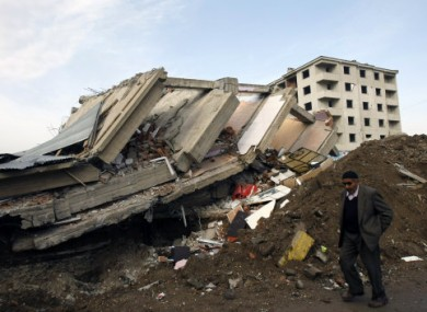 A man walks by a collapsed building in Ercis, eastern Turkey, yesterday.