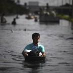 A Thai man wades through flood water as people leave flooded areas in Bangkok yesterday. (AP Photo/Altaf Qadri)
