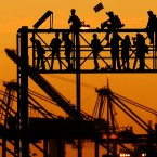Occupy Oakland protesters stand atop a railroad scaffold at the Port of Oakland yesterday. (AP Photo/Noah Berger)