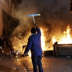 An Occupy Oakland protester holds up a sign in front of a bonfire last night. (AP Photo/Jeff Chiu)