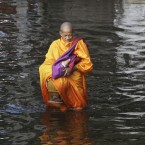 A Thai Buddhist monk, holding a bowl for morning alms, wades through floodwaters in the city's Phisi Charoen district today. (AP Photo/Sakchai Lalit)