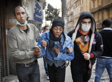 Two Egyptian protesters accompany a man, center, overcome with tear gas inhalation during the clashes with Egyptian riot police, unseen, in Tahrir square, Cairo, Egypt, today