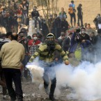 A protester runs to throw a tear gas canister away near Tahrir Square. (AP Photo/Khalil Hamra/PA Images)