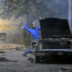 A protester throws stones during clashes with the Egyptian riot police in Cairo. (AP Photo/Khalil Hamra/PA Images)