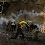 A Protester throws a tear gas canister away during clashes with the Egyptian riot police near Tahrir Square. (AP Photo/Khalil Hamra/PA Images)