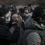 A protester overwhelmed by tear gas is aided by two men on a motorcycle during clashes with Egyptian riot police near Tahrir Square in Cairo today. (AP Photo/Tara Todras-Whitehill/PA Images)