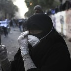A veiled woman takes pictures with her mobile phone during clashes with Egyptian riot police in Cairo. (AP Photo/Tara Todras-Whitehill/PA Images)