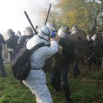 An activist clashes with riot police officers early today in Normandy as they try to block a train loaded with nuclear waste. (AP Photo/David Vincent/PA Images)