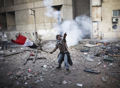 A protester points to incoming tear gas in Cairo today.