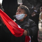 A boy with a face mask stands with his father in Tahrir Square as clashes take place nearby with Egyptian riot police. (AP Photo/Tara Todras-Whitehill/PA Images)