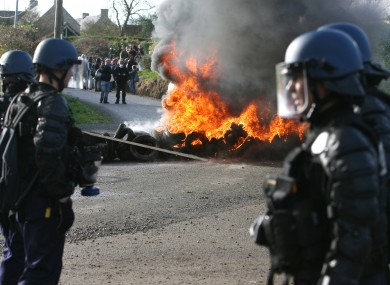 Police face protesters over a burning barricade in Normandy, France today.
