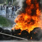 Protesters stand by a burning barricade near Lieusant, Normandy earlier today.(AP Photo/David Vincent/PA Images)